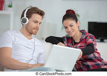 man showing something to a woman from the laptop