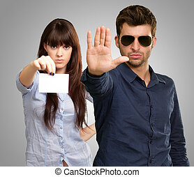 Man Showing Stop Sign In Front Of Woman Holding Placard