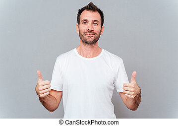 Man showing two thumbs up and looking at camera