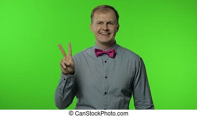 Friendly happy man showing victory sign, hoping for success and win, doing peace gesture and smiling with kind optimistic expression. Portrait of guy posing on chroma key background. People emotions