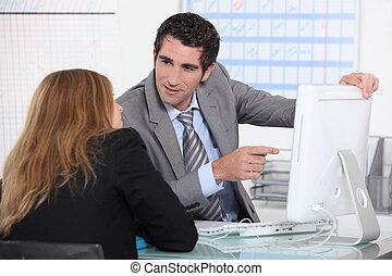 Man showing woman computer screen