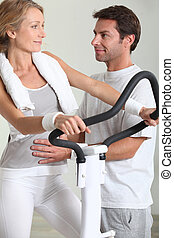 Man showing woman how to use exercise machine
