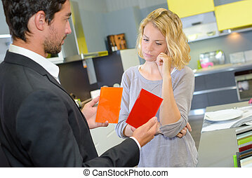 Man showing woman two colored cards