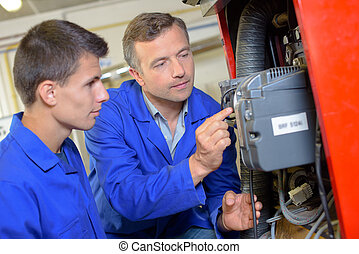 Man showing working of machinery to apprentice