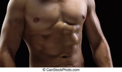 Man shows a muscular strong body close-up on a black...