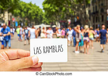 closeup of the hand of a young man showing a signboard with the text Las Ramblas, at the famous Ramblas in Barcelona, Spain