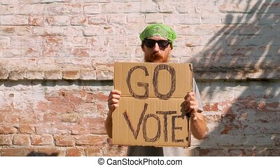 Man shows cardboard with Go Vote sign on brick wall urban background. Voting concept. Make the political choice, use your voice. Guy in bandana on face invite to go to the presidential elections.