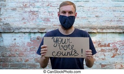 Man shows cardboard with Go Vote sign on brick wall urban background. Voting concept. Make the political choice, use your voice. Guy in protective face mask calls to go to the presidential elections.