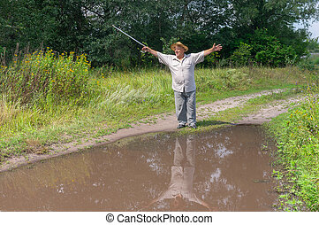 Man shows how big is a puddle on the country road