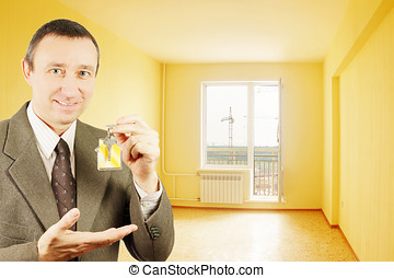 Man shows keys with keychain in the form of a little house into a new flat