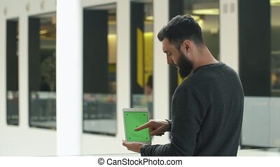 Man shows white tablet with green screen in his arms