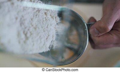 Man sifts flour close up.