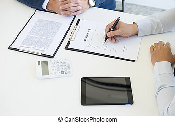 Man signing a car insurance policy, the agent is holding the document.