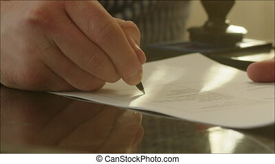 Man Signing a Contract and Setting a Stamp