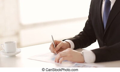 man signing a contract - man in suit and tie signing a...