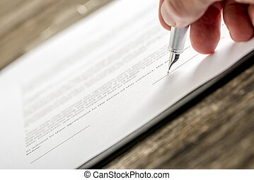 Man signing business document, subscription form or insurance papers with silver pen