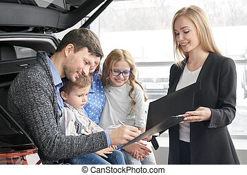 Man signing document of automobile purchase, happy family.