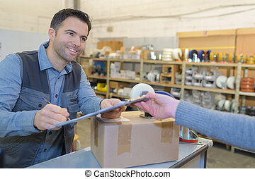 man signing for the delivery of boxes