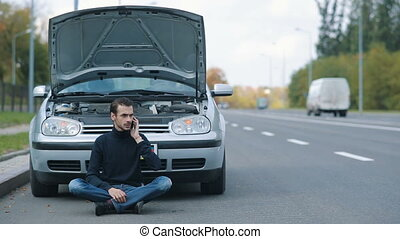 Man siitting on the road with broken