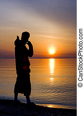 Man Silhouette at Sunrise at the Lake