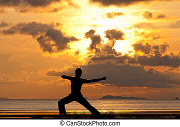 Man silhouette doing yoga exercise archer at sunset beach