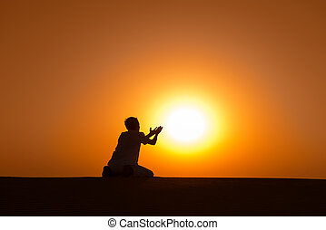 Man silhouette kneel and pray for help with gold sunset sun on background