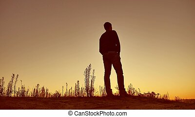 man silhouette. Man walking on summer sunset meadow. man...