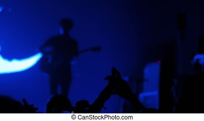 Man silhouette partying, cheering, raising hands up and clapping at rock concert in front of stage of nightclub. Bright colorful blue stage lighting. Nightlife and entertainment concept