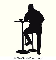 Man silhouette sitting at a table in the cafe, bar, restaurant or pub