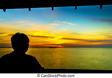 Man silhouette standing watching sunset