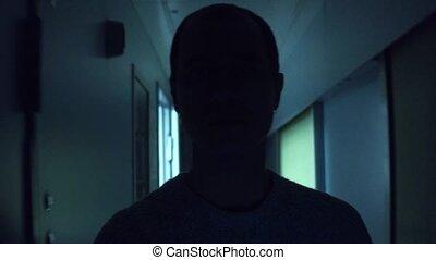 Man silhouette walking in a dark train corridor at night. 4K steadicam video