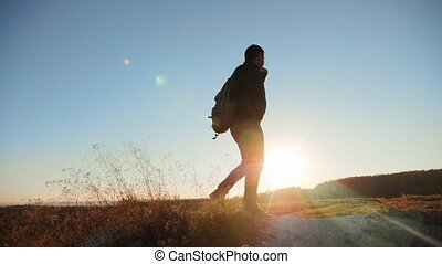 man silhouette walking tourist hiking adventure climbers sunset climb the mountain . slow motion video. hiker sunlight on top win victory the hill white rock. extreme outdoor activity sport concept tourist mountains lifestyle
