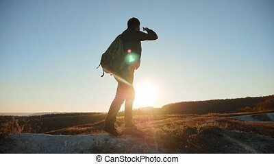 man silhouette walking tourist hiking adventure climbers sunset climb the mountain . slow motion video. hiker sunlight on top win victory the hill white rock. extreme outdoor activity sport concept tourist lifestyle mountains