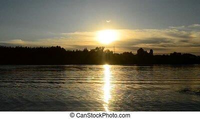 Man silhouette walks through frame on background of setting sun