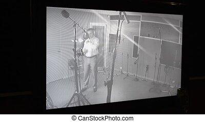 Man sing in studio in front of microphone. Surveillance...