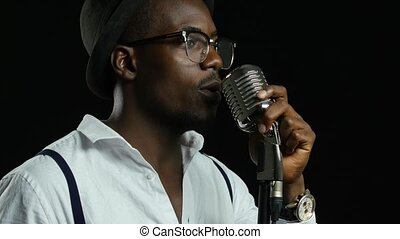 Man singer in half of the turnover sings into a microphone and dance. Black background. Close up