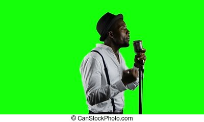 Man singer in half of the turnover sings into a microphone and dance. Green screen. Close up