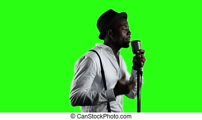 Man singer in half of the turnover sings into a microphone and dance. Green screen. Slow motion. Close up