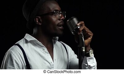 Man singer sings into a microphone and dance. Black background. Slow motion. Close up
