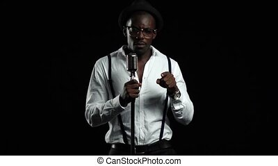 Man singer sings into a microphone and dance. Black background. Slow motion