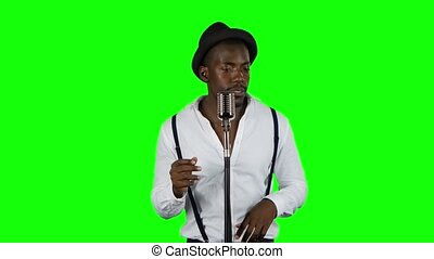 Man singer sings into a microphone and dance. Green screen