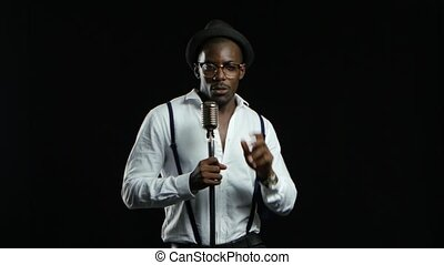 Man singer sings into a microphone and dance. Black background
