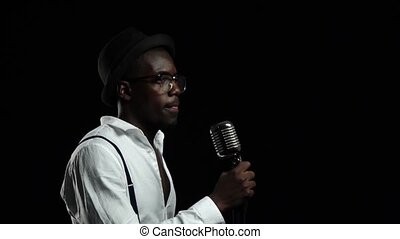Man singer sings into a microphone dance and snapping fingers. Black background. Slow motion. Close up