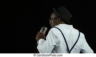 Man singer the view from the back sings into a microphone and dance. Black background. Close up