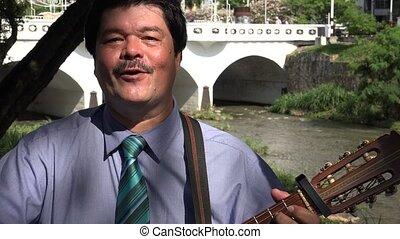 Man Singing and Playing Guitar near Bridge