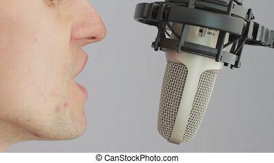 Man singing at studio microphone.