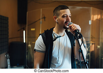 man singing into a microphone in musical rehearsal studio