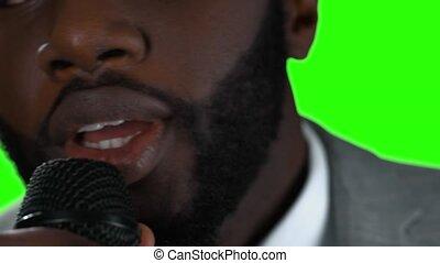 Man singing on green background.