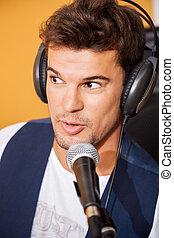 Man Singing While Wearing Headphones In Recording Studio