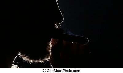 Man sipping whiskey from glass and smoking. Blacklight. Silhouette. Close up